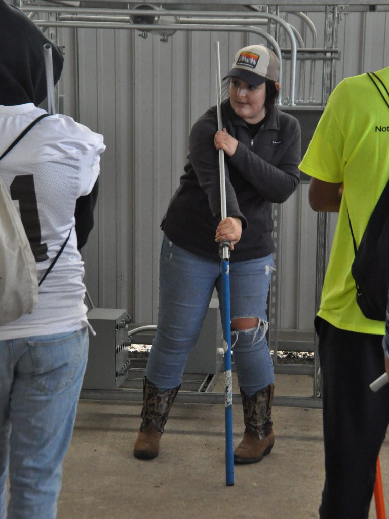 An apprentice teaches students to bend conduit at an expo.