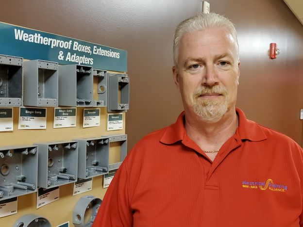 Eric Davis of the Warren Electrical JATC stands near equipment installed by apprentices.