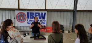 An apprentice talks with high school students about joining trades.