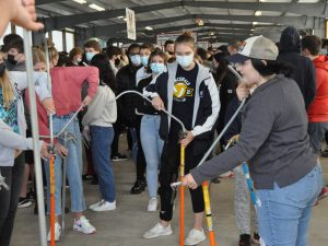 Students try bending conduit at a trades expo.