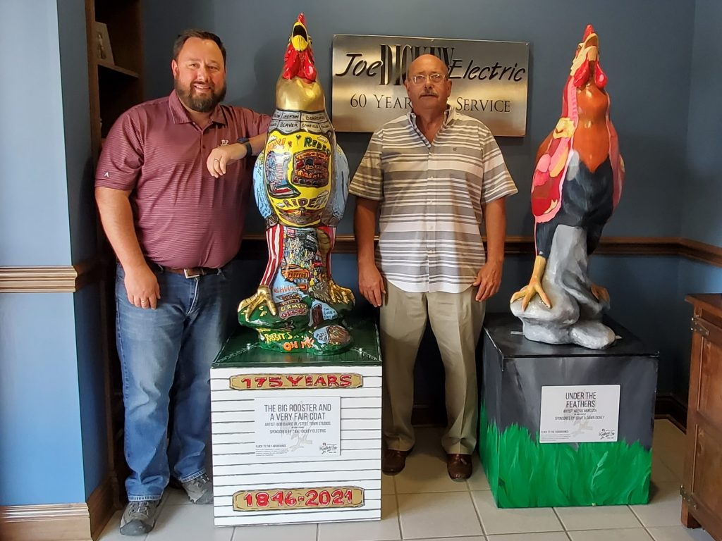 """Eric Carlson and Dave Dickey of """"Joe"""" Dickey Electric stand with rooster statues decorated by local artists."""